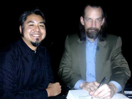 Joey deVilla smiles as Neal Stephenson autographs a book for him.