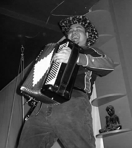 Joey deVilla plays accordion while go-go dancing on the bar at The Living Room.