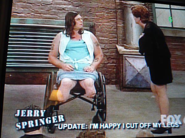 """Scene from """"Jerry Springer"""" with man in woman's clothing, sitting in a wheelchair with severed legs."""