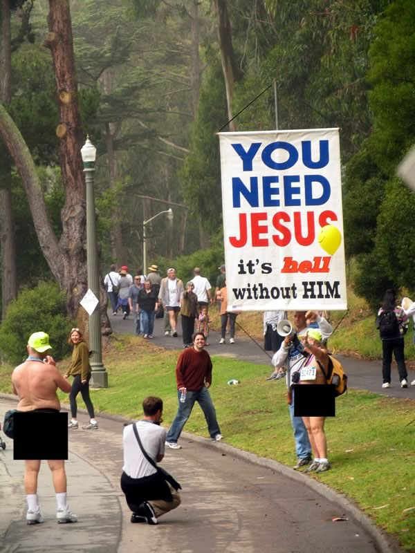 """Man holding up a """"You need Jesus / It's hell without him"""" sign in a park as he talks to an old nudist."""