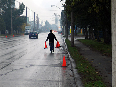 Photo of Impark employee placing pylons to block people from using free street parking