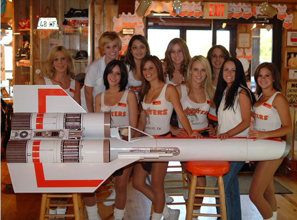 Gaggle of Hooters waitresses posing behind an old-school Battlestar Galactica Colonial Viper.