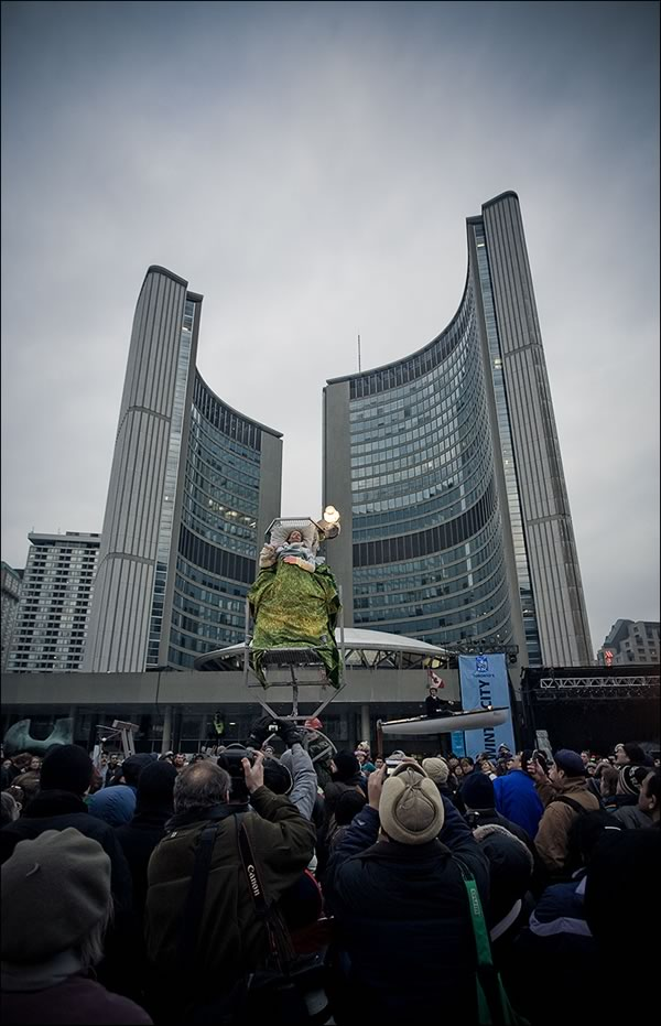 Man in bed suspended in the air with Toronto's New City Hall in the background