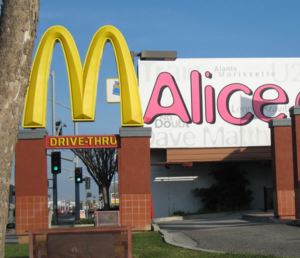 "2 signs: McDonald's ""M"" in foreground, ""Alice"" on billboard in background"