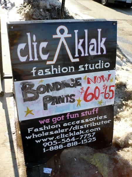 """Sandwich board on Queen West: """"Bondage Pants now $60 - 65″"""