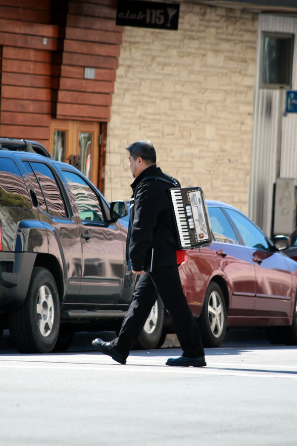 Joey deVilla, dressed all in black, walking down an Austin street with an accordion on his back.