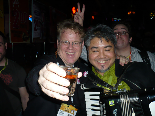 Robert Scoble with a shotglass and Joey deVilla on accordion