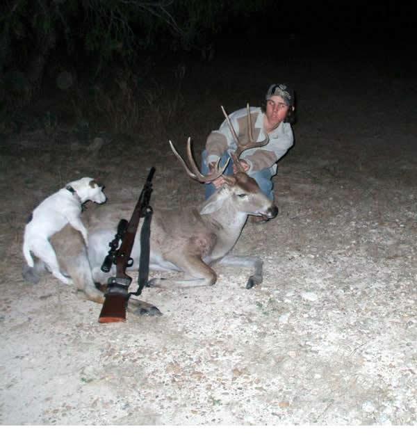Hunter posing beside a deer he shot as his dog humps it.