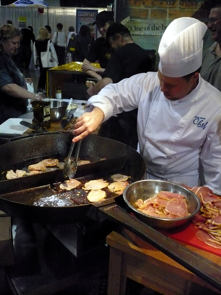 Chef frying peameal bacon in a giant iron skillet.