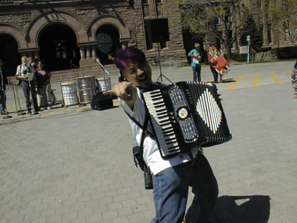 """Joey deVilla playing accordion and """"throwing the horns"""" at Queen's Park"""