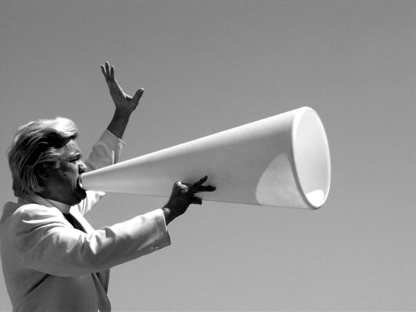 Man in white talking into a white bullhorn