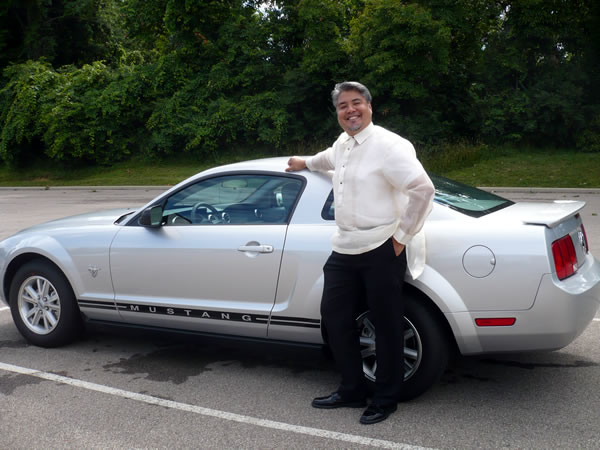 "Joey deVilla in a ""barong tagalog\"" beside a silver Mustang"