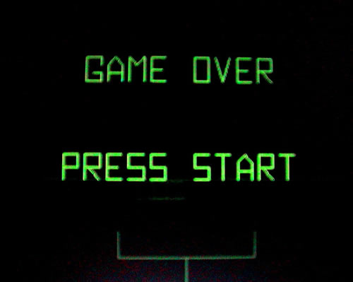 "Screen from the arcade game ""Battlezone"": ""Game Over. Press Start."""