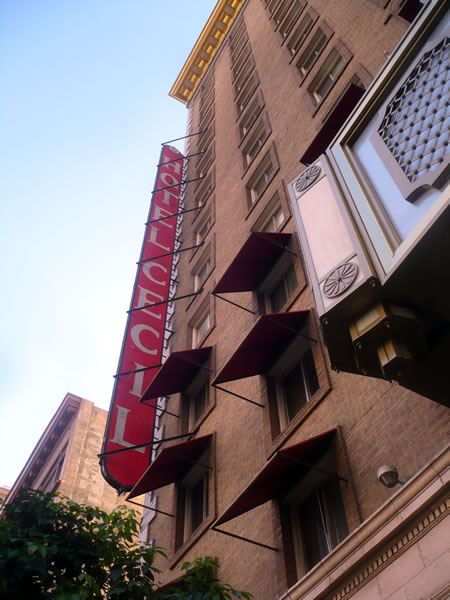 1. Exterior of the Hotel Cecil during the day, showing its vertical sign
