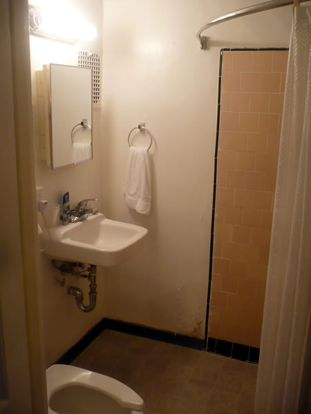 20. Hotel Cecil in-room bathroom, showing sink, toilet and shower area