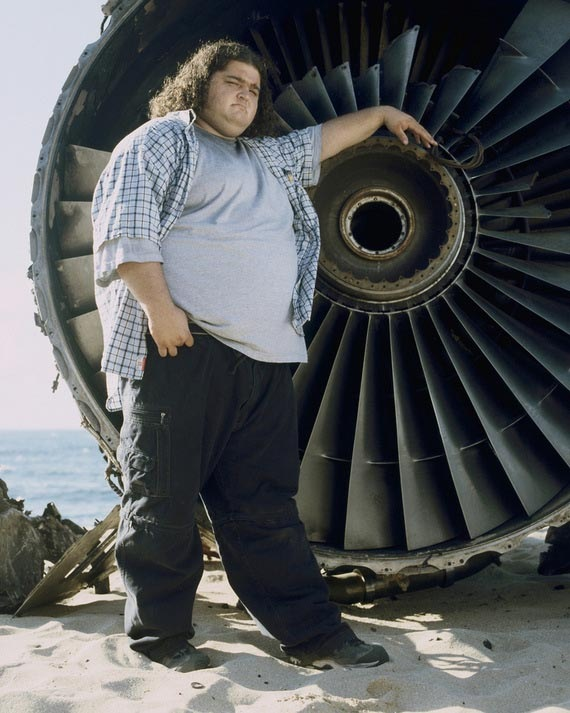 """""""Hurley"""" from the TV series """"Lost"""", posing beside one of jet engines on the beach"""