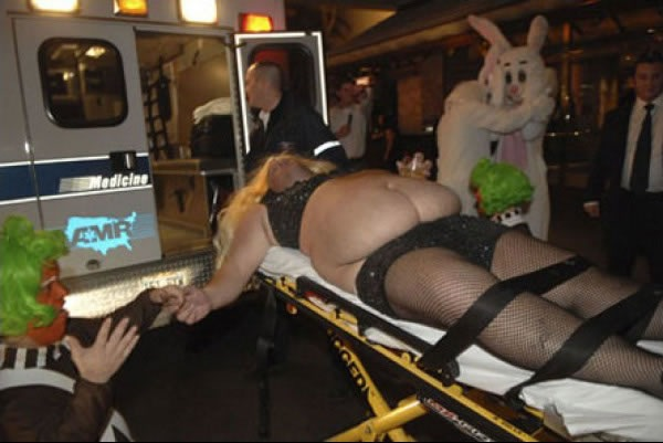 A cross-dresser strapped to stretcher is loaded onto an ambulance as a man dressed an as Oompa Loompa and two people in rabbit suits (one comforting the other) look on