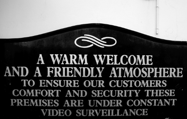 "Sign: ""A warm welcome and a freidnly atmosphere / To ensure our customers' comfort and security these premises are under constant video surveillance."""