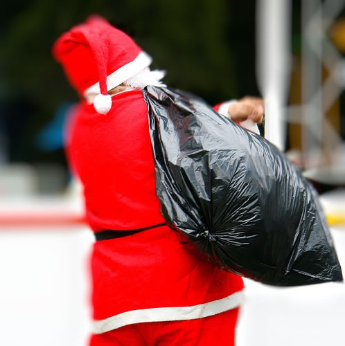 Santa, seen from behind, carrying a large trash bag