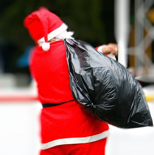 Santa, seen from behind, carrying a large trash bag