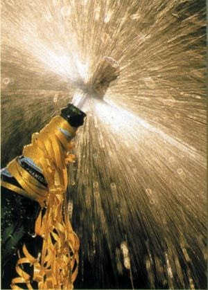 Cork popping off a ribbon-ringed bottle of champagne