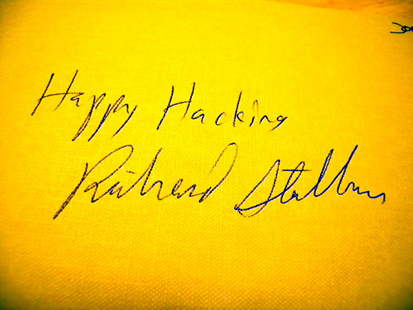 Richard Stallman's autograph, which includes the phrase 'Happy Hacking!'.