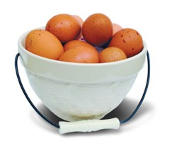 A ceramic bowl with handle, filled with brown eggs