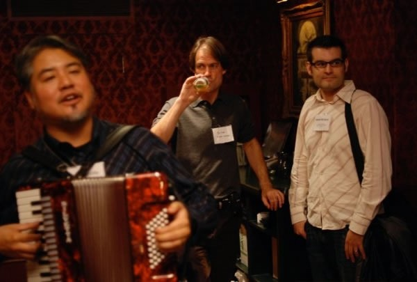 Joey deVilla plays accordion in the foreground as two guys in the background look on