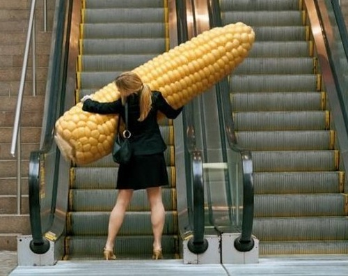Woman carrying a giant corn cob on an escalator