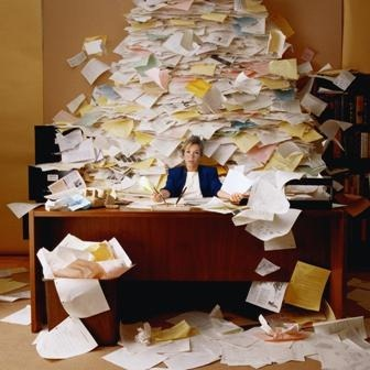 Woman at desk buried under a large pile of paperwork