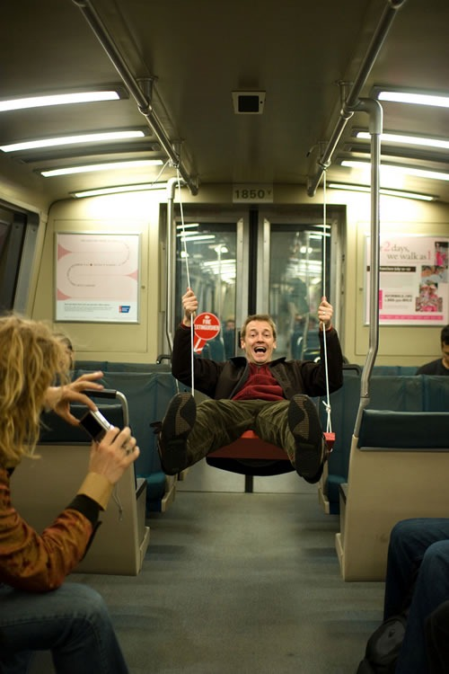 Guy on a swing hanging from the overhead rails inside a BART train car