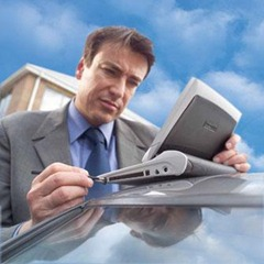 Guy using his netbook, perched on the roof of his car...with a stylus, no less!