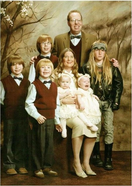 Family photo where everyone except one kid is dressed in their Sunday best; one kid us dressed like a biker/metal dude.