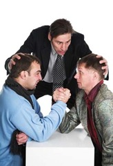 """Mediator"" photo: guy in suit acting as a referee for two guys in suits arm-wrestling"