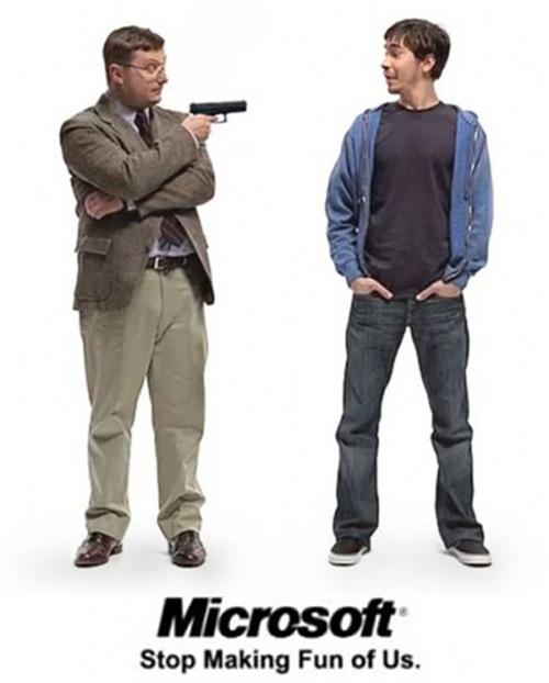 """I'm a PC"" guy holding a gun pointed at ""I'm a Mac"" guy: ""Microsoft: Stop making fun of us."""