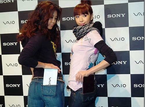 Two Japanese models trying to stuff a Sony Vaio netbook into their pockets