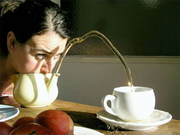 Woman with face pressed onto the top of an open teapot, blowing into it, causing tea to shoot out the spout and into a nearby cup.