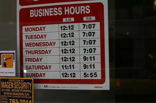 """""""Business Hours"""" sign with times that don't end on the hourr, half-hour or even quarter hour, such as """"Monday: 12:12 - 7:07""""."""