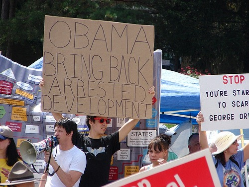 "Protestor at Town Hall holding sign that reads ""Obama: Bring back Arrested Development"""
