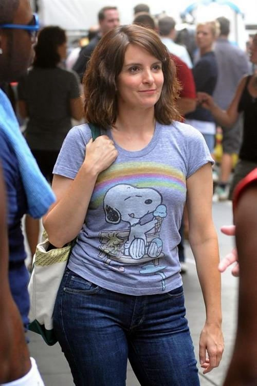 Tina Fey wearing jeans and a baby blue Snoopy and rainbow T-shirt