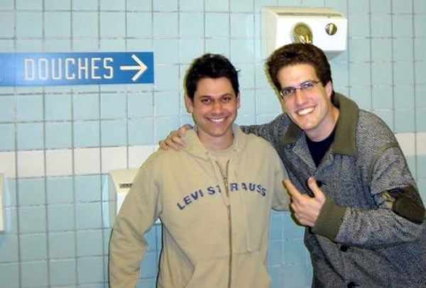 """Two guys posing beside a sign in French that points to the showers: """"Douches"""""""
