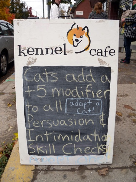 "Kennel Cafe sign: ""Cats add a +5 modifier to all persuasion and intimidation skill checks. Adopt a cat!"""