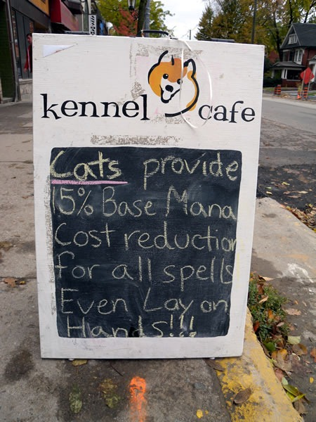 "Kennel Cafe sign: ""Cats provide 15% base mana cost reduction for all spells -- even Lay on Hands!!!"""