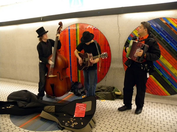 Joey deVilla playes accordion with an upright bass player and guitar player in Montreal Metro