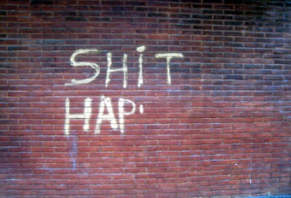 "Incomplete graffito on a brick wall: ""SHIT HAP"""