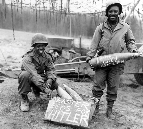 "Old black-and-white photo featuring two black WWII soldiers smiling as they display mortar shells with ""Happy Easter Adolph"" painted on them and a box labelled ""Easter eggs for Hitler"""