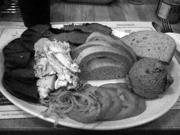 Caplansky's combo platter: grilled versht, smoked turkey, smoked meat, rye bread slices, chopped onion, tomato slices, a ball of chopped liver