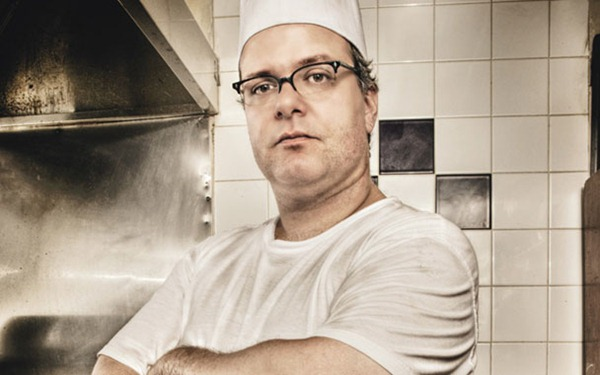 Portrait of Zane Caplansky in a chef's hat and white t-shirt, in the kitchen