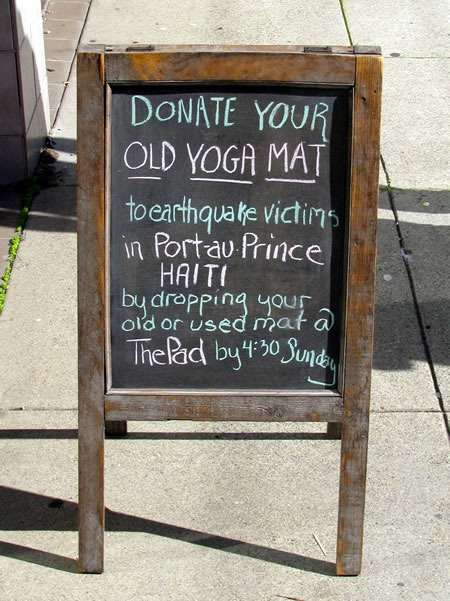 """Chalkboard sidewalk sign: """"Donate your old yoga mat to earthquake victims in Port-au-Prince, Haiti by dropping your old or used mat @ The Pad by 4:30 Sunday"""""""