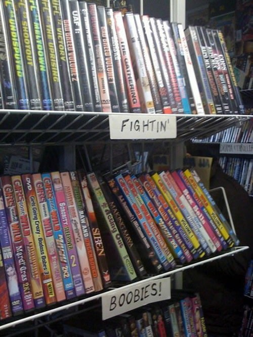Two DVD shelves at a video store, one labelled 'Fightin', the other labelled 'Boobies!'